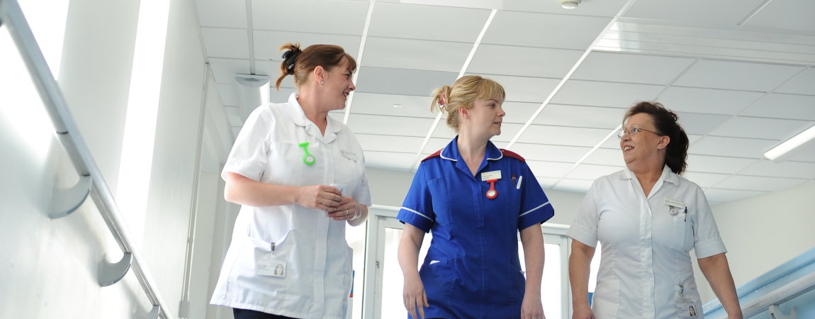 Three members of the clinical team walking along a corridor