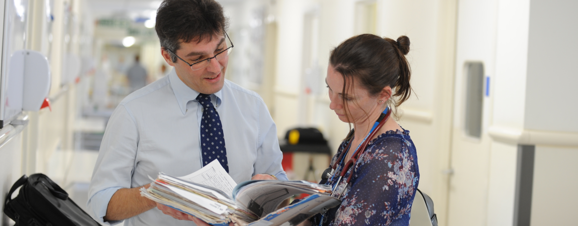 Two clinicians looking at a set of notes - click here to find out more about Overseas Visitors