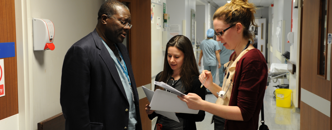 Clinical staff discussing notes in a corridor