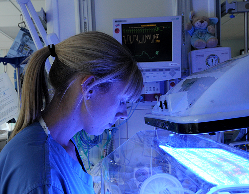 Member of NICU team by illuminated cot